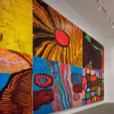 A variety of paintings on canvas by Yayoi Kusama. Each features bold colors and geometric shapes.