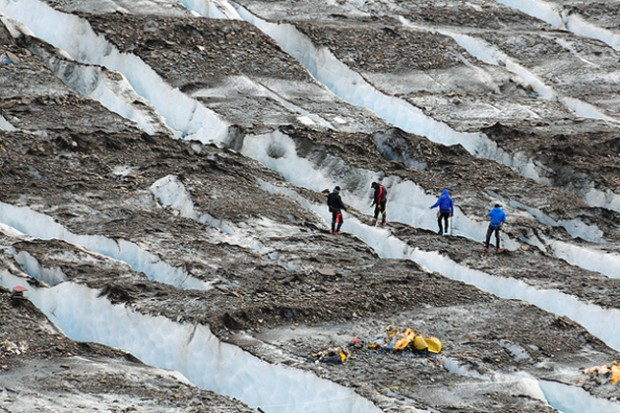 Military personnel examine a debris field on Knik Glacier, about 40 miles northeast of Anchorage, Alaska. (Photo by US Army)