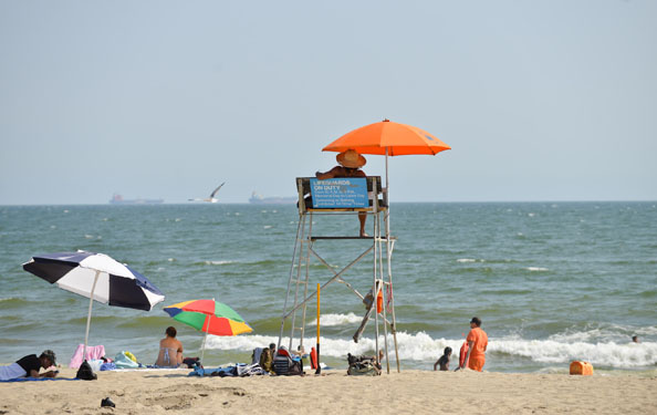 A lifeguard looks out to swimmers in the water at Rockaway Beach