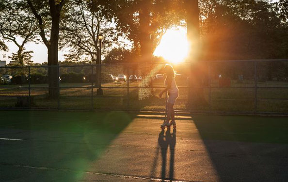 A woman rollerblades on an asphalt court in the park at sunset.