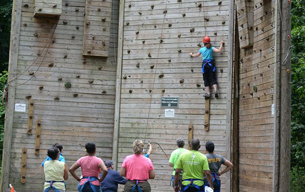 a group of people look on as a participant climbs a wall at the obstacle course