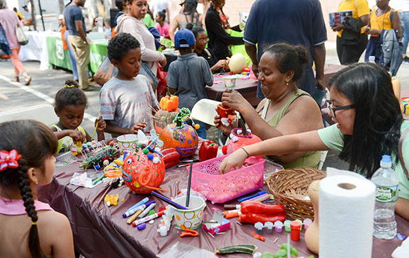 kids and adults participate in an arts and craft activity with pumpkins and stationary