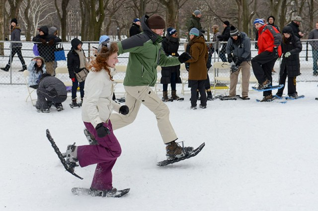 Guests practice snowshoeing at a snowfield in the park.