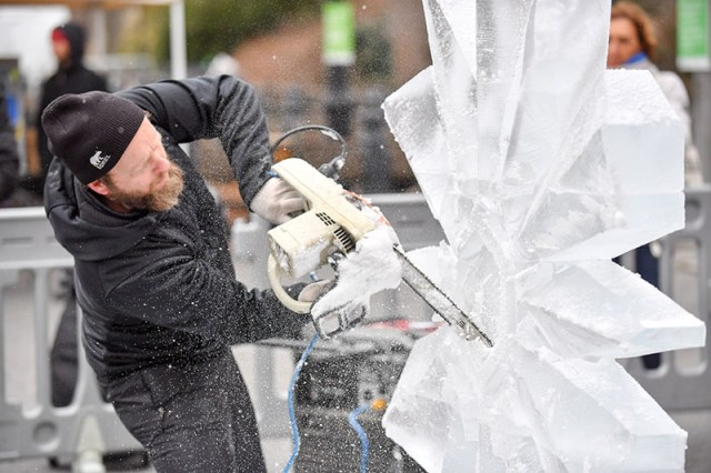 A man carves a sculpture from ice live at Winter Jam.