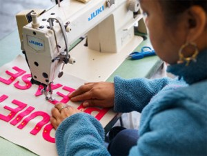 A seamstress appliques fabric letters onto a pillow in Brooklyn.
