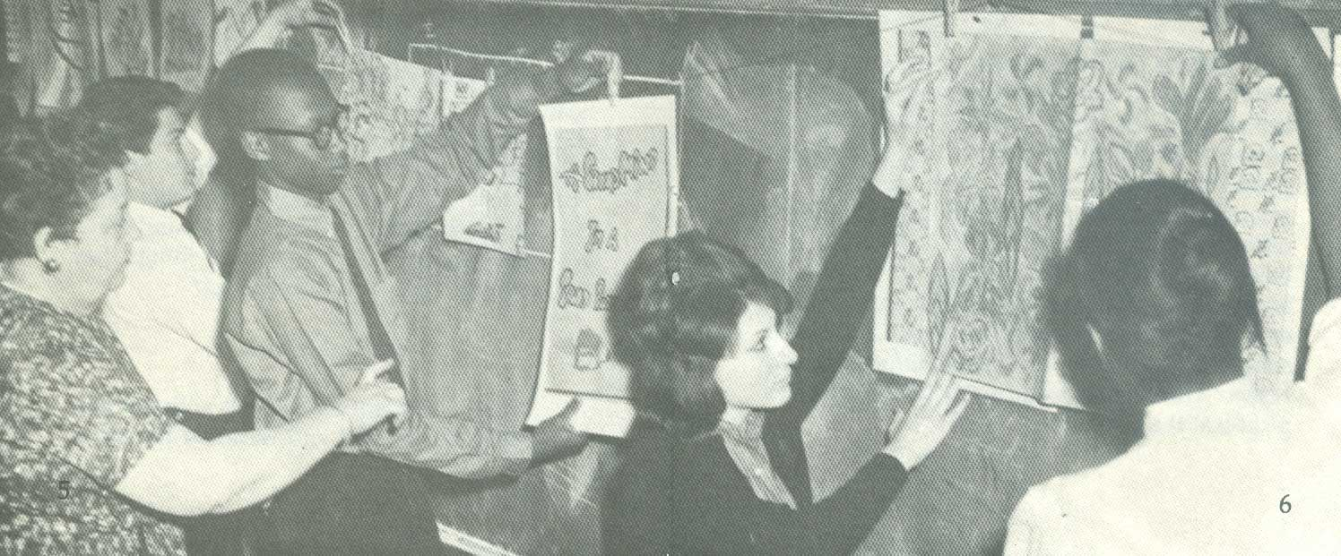 Albertina in a classroom guiding her students as they havng up artwork along the chalkboard.