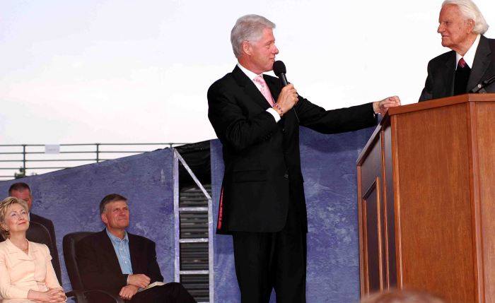 President Bill Clinton introduces Rev. Billy Graham at crusade in Flushing Meadows on June 25, 2005. Senator Hillary Clinton and Rev. Franklin Graham, seated. Photo: Tony Carnes/A Journey through NYC religions