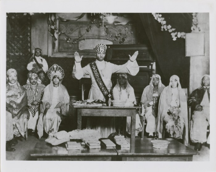 Prophet Noble Drew Ali (standing center) and temple members, at religious service of the Moorish Science Temple of America, circa late 1920s. Source: NY Public Library, Schomburg Center for Research in Black Culture