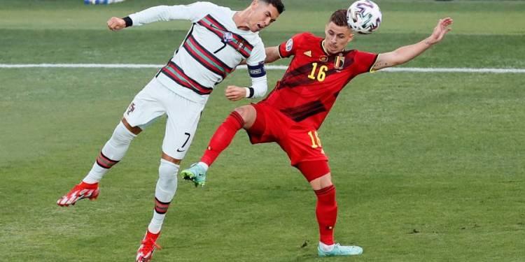 El portugués Cristiano Ronaldo, a la izquierda, compite por el balón con el belga Thorgan Hazard durante el partido de octavos de final del campeonato de fútbol Euro 2020 en el estadio La Cartuja en Sevilla, España, el domingo 27 de junio de 2021. (AP/JOSÉ MANUEL VIDAL)