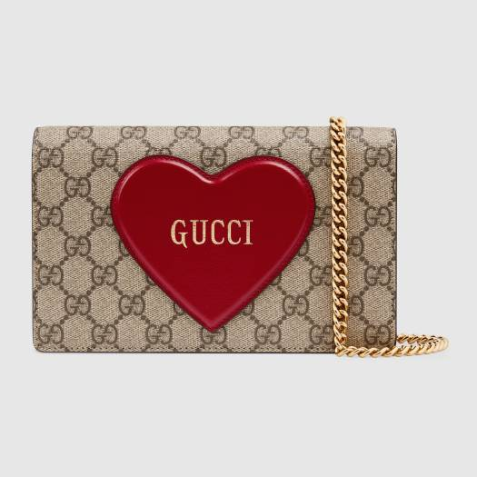 GUCCI VALENTINE'S DAY CHAIN CARD CASE WALLET | In honour of the significant occasion, Gucci presents their GG Supreme monogram canvas and a slightly over-the-top 3-D heart-shaped emblem with the Gucci logo, on this chain wallet design. It might be a little cheesy, but you know Gucci, they pull this off unexpectedly well.