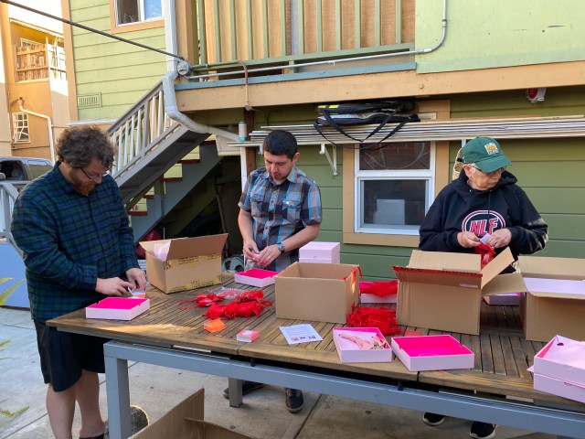 Oakland Uptown Rotary members unboxing necklaces and earrings placing into organza bags for Project Glimmer project.