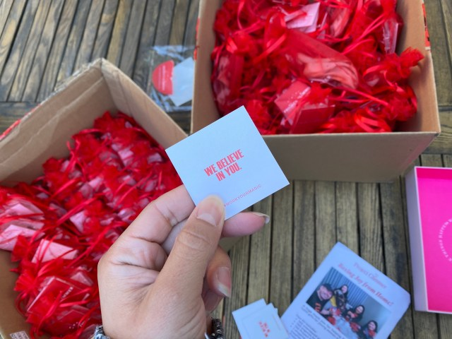 """Card that reads """"We Believe in You"""" held over two brown cardboard boxes full of red organza bags from Project Glimmer."""