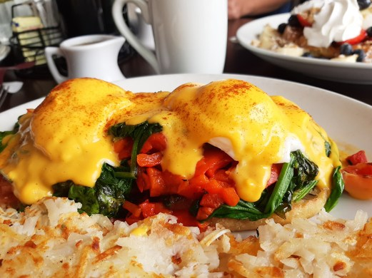 The Country Bennie at Eggsperience is an indulgent choice, but still has vegetarian allure. Poached eggs, Hollandaise sauce, fresh tomato roasted red peppers and saut?ed spinach perch atop a toasted English muffin.
