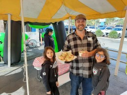 Brendan O'Connor, owner of Big Guys Sausage Stand shows off his soup and sandwich combo with his daughters, Michaela (L) and Reilly.