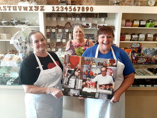 Sisters Lynn White, Sandra Figatner, and Donna Greenwald show off a picture of their parents in their Berwyn candy shop.
