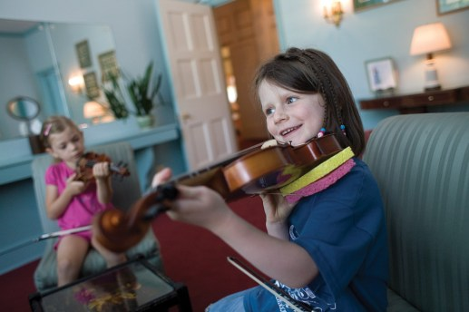 No-sweat fret: Sadie Collins, right, works on putting her fingers in the right place during the Oak Park Fiddle Camp at the 19th Century Charitable Association on July 3. The camp hosted 14 kids, who learned violin, guitar and contra dancing.Photos by David Pierini/Contributor