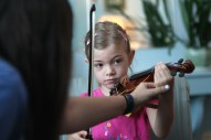 Rebecca Baiman, above, helps Meredith Steinman place her hand during the Oak Park Fiddle Camp.