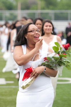 A graduate smiles as she spots family in the stands.