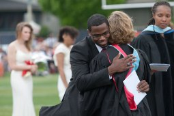 A graduate hugs counselor Heidi Lynch as he receives his diploma.