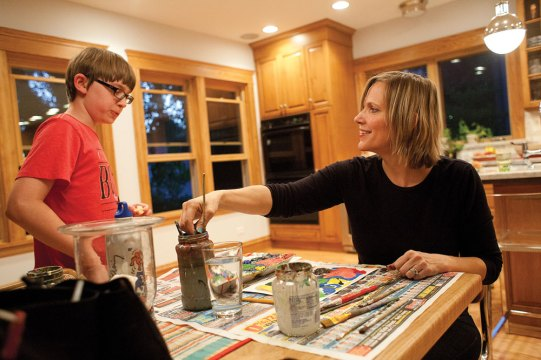 Kathryn Hempel, right, talks to her son, Lincoln Warner, while she paints at her kitchen table in Oak Park. Hempel is attempting to create one piece of art every day for a year.
