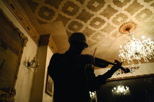 Fred Donini-Lenhoff plays violin during a recent gig at Klas Restaurant in Cicero. Donini-Lenhoff incorporates violin into his act as rapper Freddy Flow. (David Pierini/staff photographer)