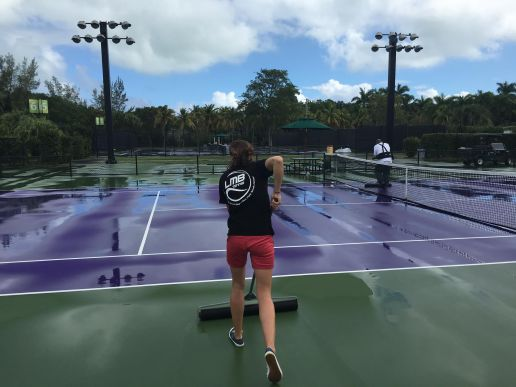 Mirka Bagos, the Oak Park Tennis Center's Junior Tennis Director and Club Manager, prepares one of the courts at the Junior Orange Bowl with a squeegee. (Courtesy Luka Bagos)