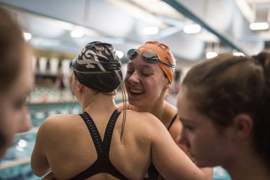 OPRF senior sprint and relays swimmer Natalie Ungaretti, right, hugs a Fenwick swimmer. The Friars and Huskies finished first and second, respectively, at the Fenwick Sectional. (Alexa Rogals/Staff Photographer)