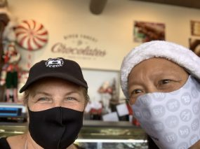 Donna Fantetti-Slepicka. owner of River Forest Chocolates, is all smiles under her mask after a gift card purchase made by Susie Goldschmidt.