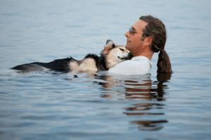 John Unger faz relaxar nas águas mornas do Lago Superior seu cão, Schoep, afetado por dores fortíssimas causadas por artrite e um câncer no quadril: a foto tornou-se viral, a história dos dois rodou o mundo -- e agora, aos 20 anos, Schoep morreu (Foto: Hannah Stonehouse Hudson)