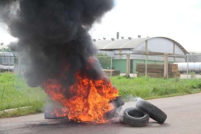 Funcionários queimaram pneus em frente ao portão de acesso em protesto pelo atraso de pagamentos - Fotos: Alexandre Lima