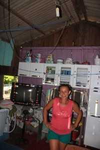 Dona Raimundo mostra sua casa com apenas uma lâmpada, uma geladeira e uma televisão.