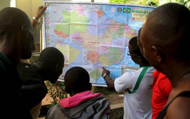 A foto escolhida para ilustrar o livro foi a que mostra refugiados haitianos apontando em um mapa do Brasil /Foto: Odair Leal