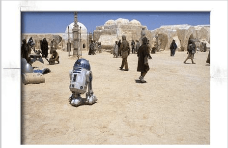 From starwars.com: R2-D2 cautiously threads his way through dangerous passersby on his way to an important meeting. A droid has to be careful in rough towns like this one.