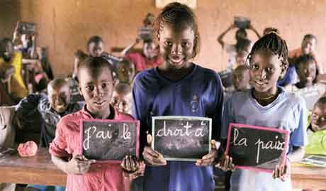 """A realização dos direitos da criança é fundamental para criar o mundo idealizado pela Declaração do Milênio – um mundo de paz, igualdade, tolerância, segurança, liberdade, solidariedade, respeito pelo meio ambiente e responsabilidade compartilhada. """"Eu tenho direito à paz"""", dizem as lousas que estas crianças seguram na sala de aula, na Escola Primária Kabiline I, no vilarejo de Kabiline, no Senegal.(Imagem: UNICEF)"""