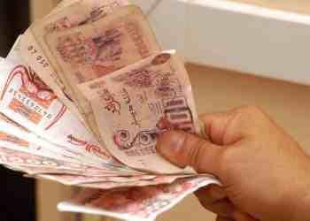 Main tenant un éventail de billets de 500 dinars et de 1000 dinars.