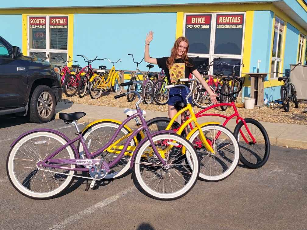 Smiling employee waving with purple, yellow and red rental bikes out front of store