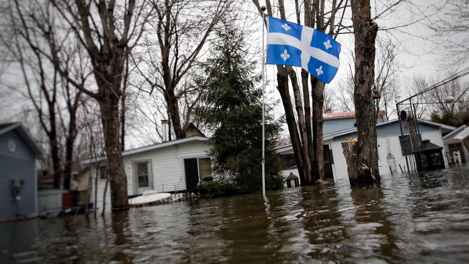 Un drapeau du Québec flotte sur un mât dans un quartier résidentiel complètement inondé.
