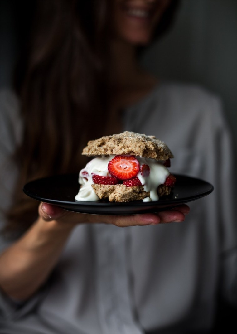 Strawberry shortcake on plate being held in front of woman.
