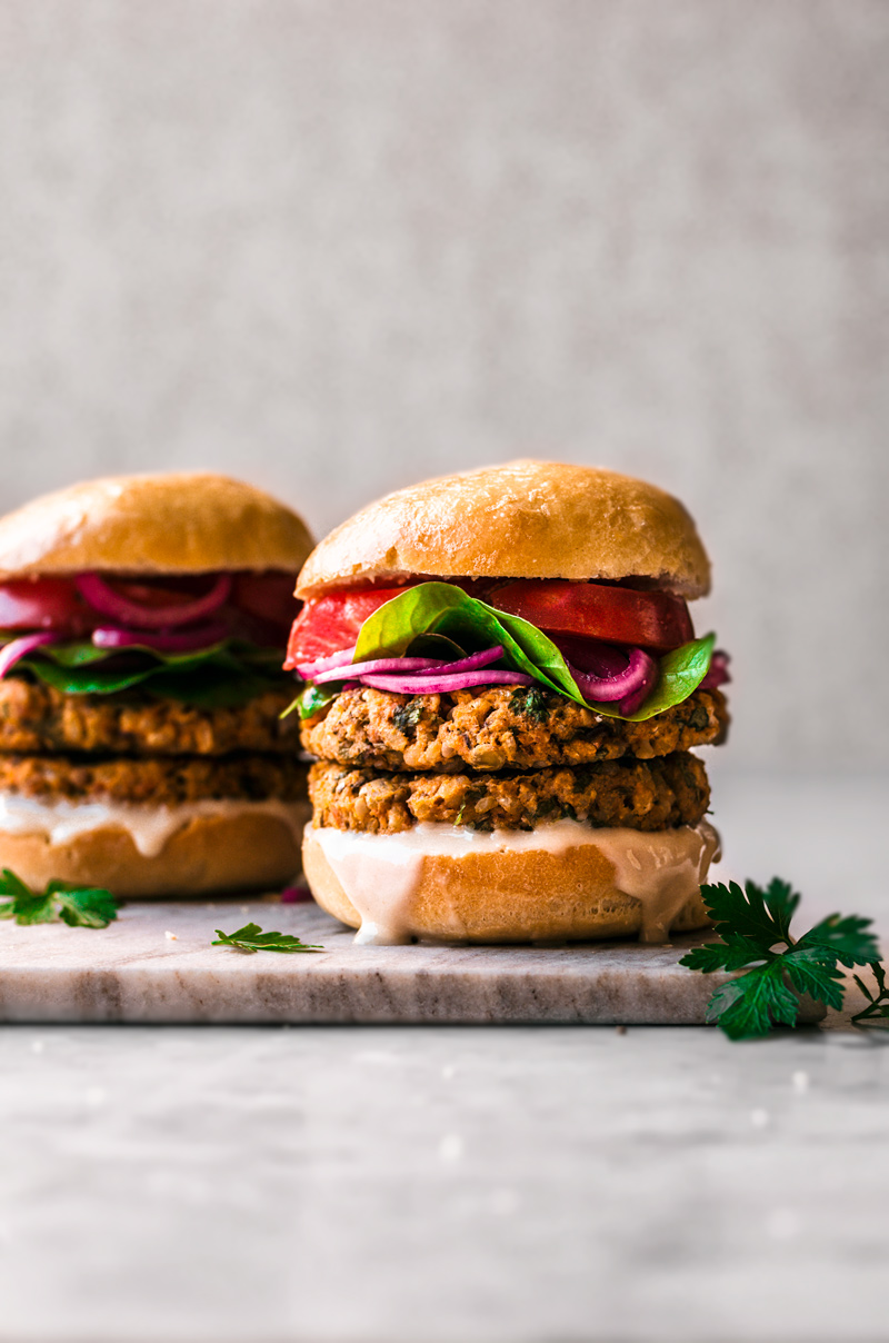 Double stacked sweet potato burger with greens, pickled onions, and tomatoes on a bun.