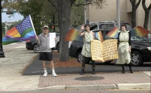Stoll protesting First Baptist Church in Jacksonville with a Rainbow flag.
