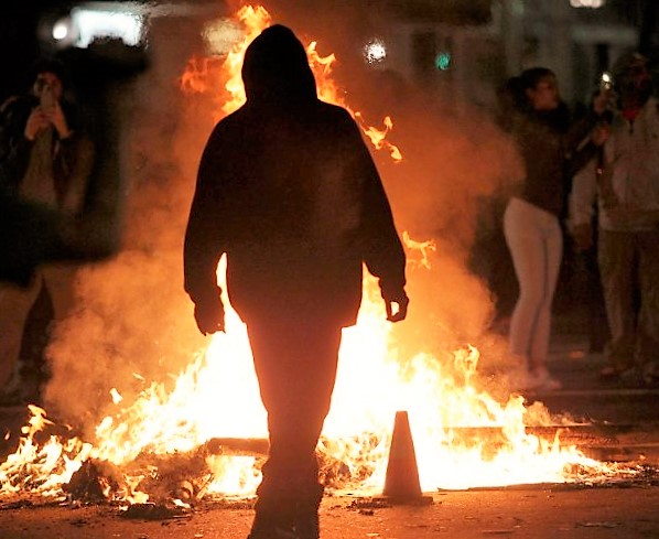 A protester walks past a fire burning along Broadway at 17th Street following a mostly peaceful march in demonstration against President-elect Donald Trump in Oakland, Calif., on Wednesday, Nov. 9, 2016. (Anda Chu/Bay Area News Group)