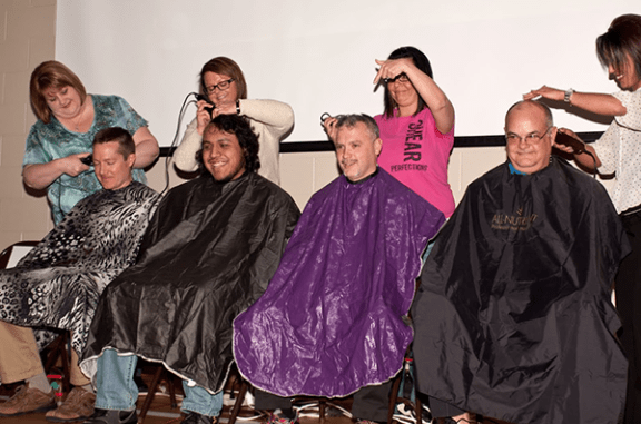 """Hart's Spitler Elementary staff, left to right, Aaron Schlukebir, Leo Martinez, Todd Hamilton and Tom Stoneman get their heads shaved as part of a """"March is National Reading Month"""" event."""