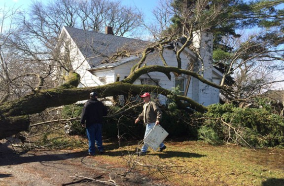 Bert VandenHuevel and his son, Logan, clean up damage at their Weare Twp. home.