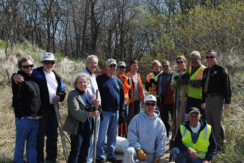 Property owners, members of the Oceana County Road Commission, road commission workers and Oceana County Sheriff Bob Farber gather in Claybanks Township where Whiskey Creeks flows into Lake Michigan Monday to put up poles that define public right-of-way.