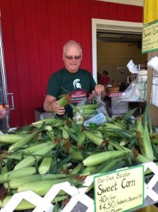 Rick Emerson of Lansing, who has a vacation home in Oceana County, shops for sweet corn at Rennhack Orchards Market in Hart.