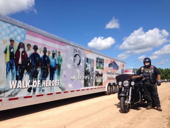 Vietnam veteran Bill Errante stands next to the Traveling Vietnam Wall at the Oceana County Fairgrounds in Hart.