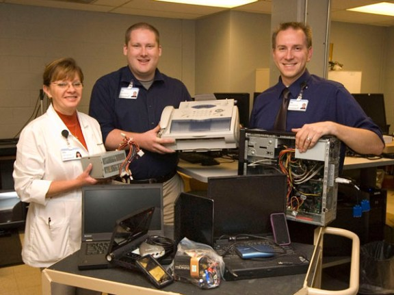 Members of the hospital information services department display samples of electronic items that can be recycled this Friday and Saturday. From left, Cathy Beckett, lead clinical analyst, Will Hagerty, systems administrator, and Chip Bowden, network administrator.