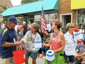 Doug Bacon, at left, is among club members who helped a team of local volunteers collect fireworks donations during Pentwater's 2014 Homecoming Parade.