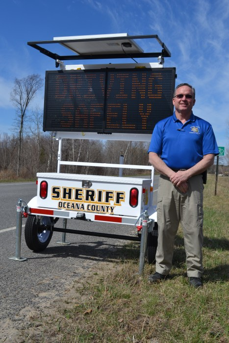 Oceana County Sheriff Bob Farber stands next to the new traffic safety awareness trailer acquired by the sheriff's office through a grant from AAA for nearly $17,000.