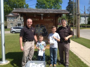 Oceana County Sheriff Bob Farber and Deputy Dave Gregwer receive police week survival kits from Wyatt and Lincoln Furman.